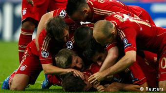 Bayern Munich's Thomas Mueller (bottom) celebrates with team mates his goal against Chelsea.