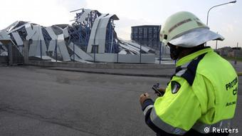 A rescue worker patrols in front of a ceramics factory building which was damaged by the earthquake