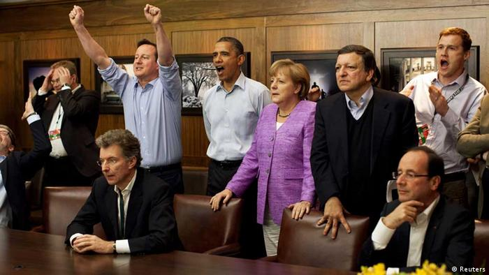 Prime Minister David Cameron of Britain (centre L-R) , President Barack Obama, Chancellor Angela Merkel of Germany, Jose Manuel Barroso, President of the European Commission, and others watch the overtime shootout of the Chelsea vs. Bayern Munich Champions League final in the Laurel Cabin conference room during the G8 Summit at Camp David, Maryland, May 19, 2012. REUTERS/White House/ Pete Souza/POOL