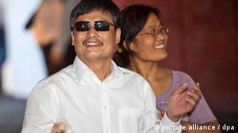 Chen Guangcheng, blind Chinese human rights activist and his wife Yuan Weijing smile as they arrive at a New York University housing