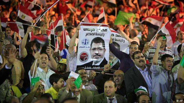 Egyptian supporters of Mohammed Morsi, Muslim Brotherhood's presidential candidate, wave posters of him with Arabic that reads, Mohammed Morsi for Egyptian presidency, during a campaigning conference in Cairo Egypt.