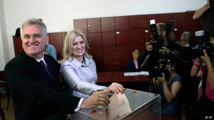 Tomislav Nikolic, left, the nationalist Serbian Progressive Party leader and presidential candidate, and his wife, Dragica, center, cast their ballots at the presidential run-off elections in Belgrade, Serbia
