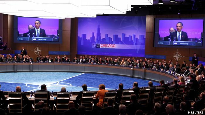 U.S. President Barack Obama is shown on large screens as the NATO Summit gets underway in Chicago, May 20, 2012. REUTERS/Larry Downing (UNITED STATES - Tags: POLITICS MILITARY)