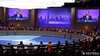 U.S. President Barack Obama is shown on large screens as the NATO Summit gets underway