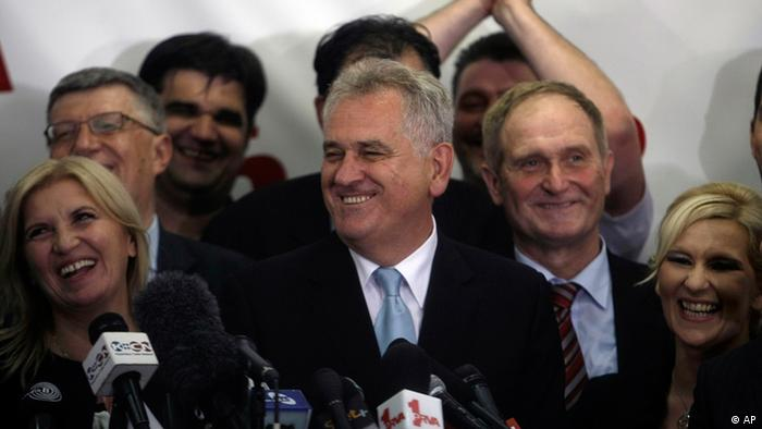 Tomislav Nikolic, center, the nationalist Serbian Progressive Party leader and presidential candidate, smiles as he talks to members of the media after claiming victory at the presidential runoff elections in Belgrade, Serbia, Sunday, May 20, 2012, with his wife, Dragica at left. Nationalist Nikolic beat pro European Union incumbent Boris Tadic in Serbia's presidential runoff election. (Foto: Marko Drobnjakovic/AP/dapd)