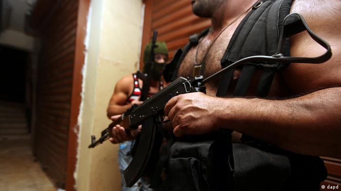 Anti-Syrian gunmen stay put near buildings during overnight clashes between pro and anti Syrian Sunni groups in Beirut, Lebanon, Monday, May 21, 2012.