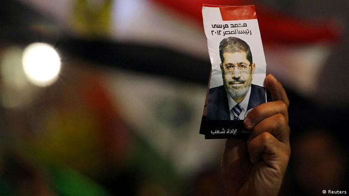 A supporter of Mohamed Mursi, the head of the Muslim Brotherhood's political party and the Brotherhood's presidential candidate, holds a flyer of Mursi