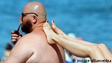Sommerfrische am Schwarzen Meer bei Sotschi Pfeife rauchend genießt ein dicker Mann mit seiner Frau am 24.06.2005 einen Tag an einem Strand bei Sotschi am Schwarzen Meer. Foto: ITAR-TASS / Valery Matytsin +++(c) dpa - Report+++