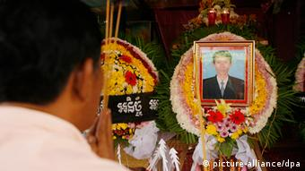 A Cambodian man prays in front of a portrait of Chut Wutty,
