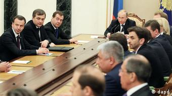A half-dozen men in business suits sit around a wooden table in a serious, business-like setting. (Photo:RIA-Novosti, Yekaterina Shtukina, Presidential Press Service/AP/dapd)