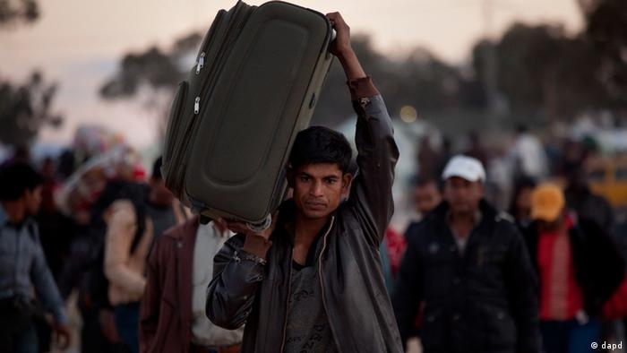 A man from Bangladesh, who used to work in Libya and fled the unrest in the country, carries his belongings as he arrives in a refugee camp after crossing from Libya at the Tunisia-Libyan border, in Ras Ajdir, Tunisia, Monday, March 21, 2011. (Foto:Emilio Morenatti/AP/dapd)