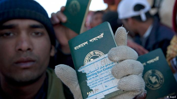 Refugees from Bangladesh show their passports after crossing the Libya-Tunisia border in Ras Ajdir, Tunisia, Wednesday, March 2, 2011
