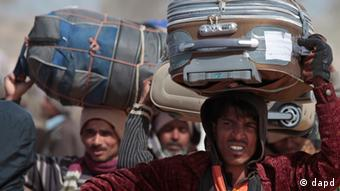 Men from Bangladesh, who used to work in Libya and fled the unrest in the country, carry their belongings as they arrive in a refugee camp at the Tunisia-Libyan border, in Ras Ajdir, Tunisia, Wednesday, March 9, 2011