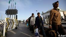 Migrant workers from Bangladesh and Sri Lanka walk on the Libyan side of the Ras Adjir border before crossing into Tunisia, in Libya Thursday, March 3, 2011. About 12,000 people have been crossing the Libyan-Tunisian border daily this week, and in total between 20,000 and 30,000 migrants were now in Ras Adjir, according to the Tunisian Red Crescent. (Foto:Ben Curtis/AP/dapd)