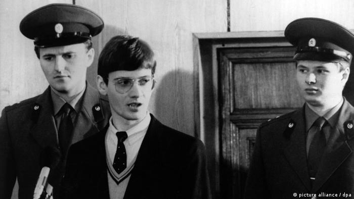 Dois policiais e um rapaz de óculos e cabelos curtos