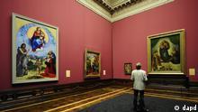 Ein Teilnehmer einer Vorbesichtigung betrachtet am Montag (05.09.11) im Semperbau des Zwingers in Dresden in der Galerie Alte Meister der Staatlichen Kunstsammlungen Dresden (SKD) in der Ausstellung Himmlischer Glanz. Raffael, Duerer und Gruenewald malen die Madonna das Gemaelde Die Sixtinische Madonna (1512/13, r.) des italienischen Malers Raffael (1483-1520), waehrend links das Gemaelde Madonna di Foligno (1511/12) von Raffael haengt. In der Schau Himmlischer Glanz. Raffael, Duerer und Gruenewald malen die Madonna werden bis 8. Januar 2012 wertvolle Madonnenbildnisse aus der Renaissance gezeigt. (zu dapd-Text) Foto: Norbert Millauer/dapd