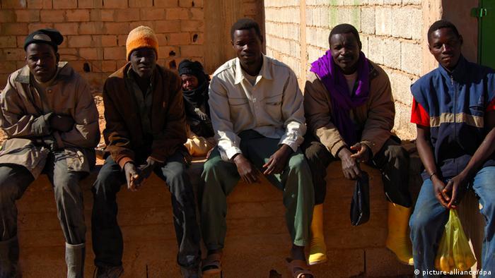 Arbeitslose afrikanische Männer sitzen auf einer Mauer, Germa, Libyen