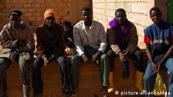 Arbeitslose afrikanische Männer sitzen auf einer Mauer Foto: dpa