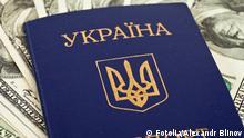 Symbolbild Ukrainischer Pass auf amerikanischem Dollar