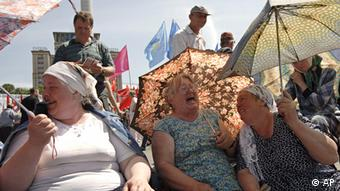 Elderly women with umbrellas on a sunny day