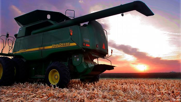 Photo of a John Deere combine on a harvested US cornfield at sunset
