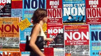 A woman walks past posters urging France to vote no to the European constitution
