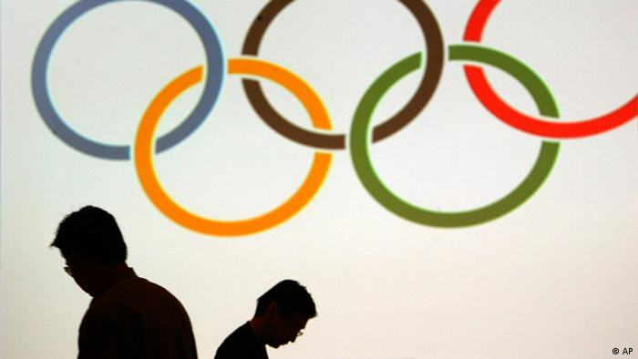Силуэты на фоне олимпийских колец