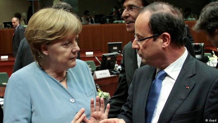 French President Francois Hollande, right, talks with German Chancellor Angela Merkel, prior to the start of an EU summit, at the European Council building in Brussels, Wednesday, May 23, 2012.
