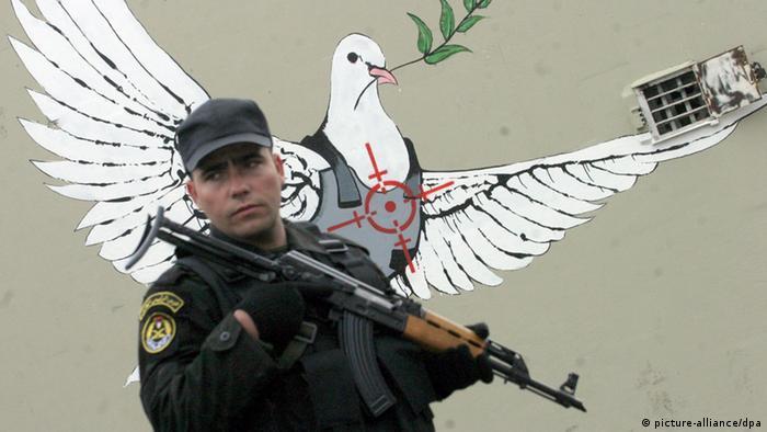 Ein Soldat mit Gewehr steht vor einer Mauer, auf die eine Friedenstaube gemalt ist