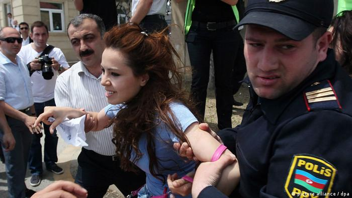 Azerbaijani police officers in uniform and in civil detain an opposition supporter during an anti-government protest in central Baku, Azerbaijan