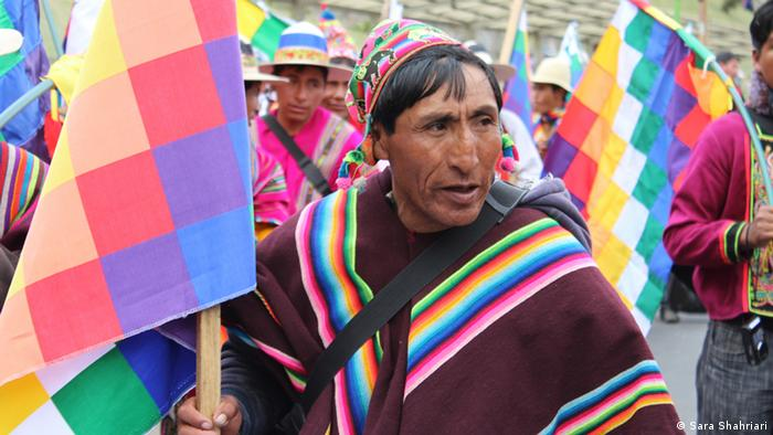 Indigenous Bolivian marches with colorful flag