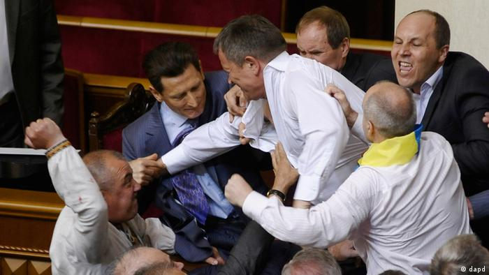 Lawmakers from pro-presidential and oppositional factions fight in the parliament session hall in Kiev.