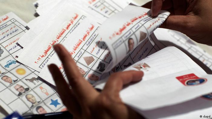 An Egyptian election official counts the ballots following the presidential election in Cairo, Egypt, Thursday, May 24, 2012. As vote-counting began, exit polls by several Arab television stations suggested the Brotherhood's Mohammed Morsi was ahead of the pack of 13 candidates. The reliability of the various exit surveys was not known, and a few hours after the end of two days of voting, only a tiny percentage of the ballots had been counted. (AP Photo/Fredrik Persson)
