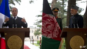 French President Francois Hollande, left, gestures during a joint press conference with Afghan President Hamid Karzai