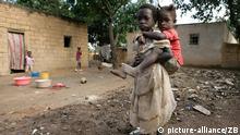 In der Provinzhauptstadt Huambo trägt ein Mädchen sein Geschwisterkind nach Hause