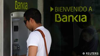 A man withdraws money from an ATM at a Bankia branch in Madrid