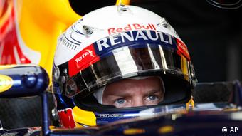 Red Bull driver Sebastian Vettel of Germany looks on in the pit