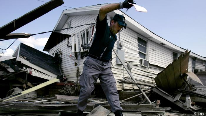 Paris, Maine, firefighter Stan Larson tries to keep his balance as he makes his way across debris to place a red sticker on a flood-damaged home in the lower Ninth Ward of New Orleans Saturday, Oct. 1, 2005. (Photo: ddp images/AP Photo/Charlie Riedel)