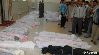 The bodies of people whom anti-government protesters say were killed by government security forces lie on the ground in Houla