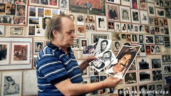 Ein Autogrammsammler vor einer Wand mit seinen zahlreichen Sammelstücken. Foto: DW
