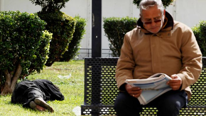 A homeless man lies on a lawn in Athens' central square as a man reads his newspaper at a bus stop, Tuesday Oct. 11, 2011.