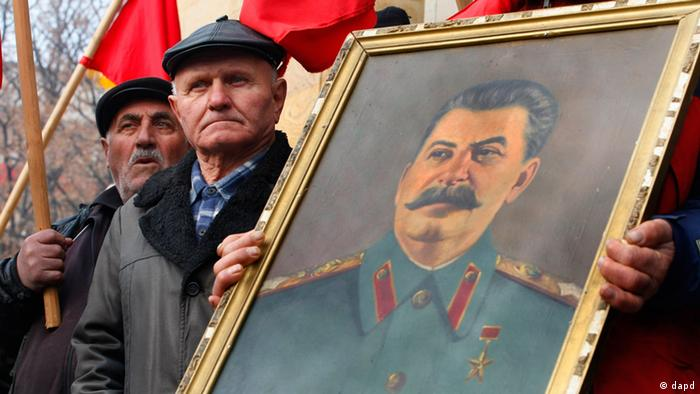 A Georgian holds a portrait of Soviet dictator Joseph Stalin during a rally marking Stalin's 132nd birthday anniversary