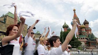 Opposition supporters wave white ribbons at a protest on Red Square in Moscow