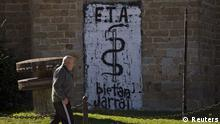 A man passes in front a wall painted with the symbol of the Basque separatist armed group ETA, reading '' ETA. Together Always '', in Arbizu northern Spain Friday Oct.21, 2011, the day after ETA announced the end of its armed struggle. (ddp images/AP Photo/Alvaro Barrientos). // eingestellt von se