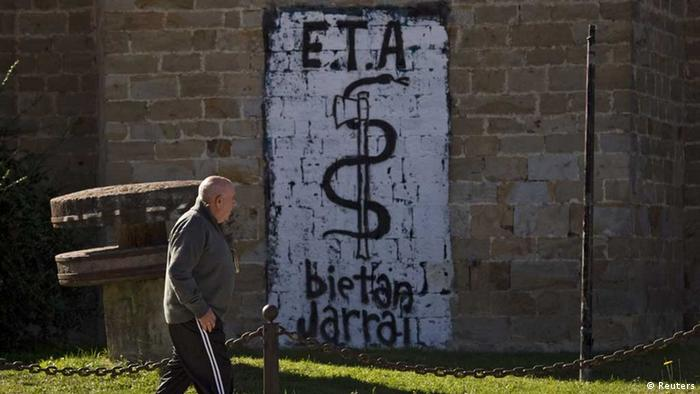 A man passes in front a wall painted with the symbol of the Basque separatist armed group ETA, reading ETA. Together Always, in Arbizu northern Spain