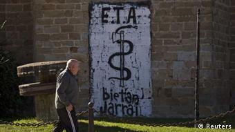 Человек смотрит на лозунг группировки ЭТА, написанный на стене