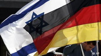 A worker prepares an Israeli, left, and a German, right, flag in front of the Knesset prior to the speech of German President Horst Koehler in the Israeli parliament in Jerusalem on Wednesday, Feb. 2, 2005. (ddp images/AP Photo/ Markus Schreiber)
