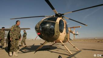 In a desert setting, a soldier walks up to a helicoper that's either preparing for takeoff or just landing. (Photo: DW)