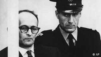 Nazi criminal Adolf Eichmann is seen standing in his bullet proof glas box as the charges against him are read during judical proceedings in the Beit Ha'Am building in Jerusalem, Israel, April 12, 1961. Next to him stands a security officer. (AP Photo/Str) --- Zur Eroeffnung der Anklage gegen Adolf Eichmann im Verhandlungssaal des BeitHa'Am Gebaeudes in Jerusalem, Israel, steht Eichmann in seiner Anklagekabine hinterPanzerglas, neben ihm ein Sicherheitsbeamter am 12. April, 1961. (AP Photo/Str)