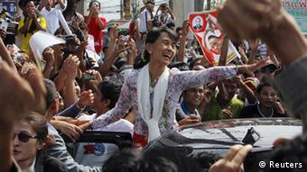 Myanmar's pro-democracy leader Aung San Suu Kyi greets migrant workers from Myanmar, as she visits them in Samut Sakhon